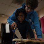 Atlas Pyke, a volunteer with Hollistc Me, helps Iyonna Bridges, 7, first grade, saw a piece of wood for her woodworking projcet. --Education Week/Deanna Del Ciello